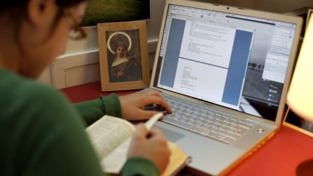 femme travaillant sur ordinateur avec photo de Sainte Rita.